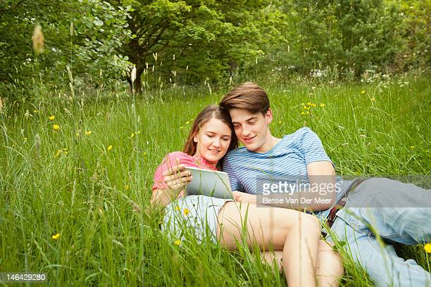 couple looking at ipad while laying in grass.