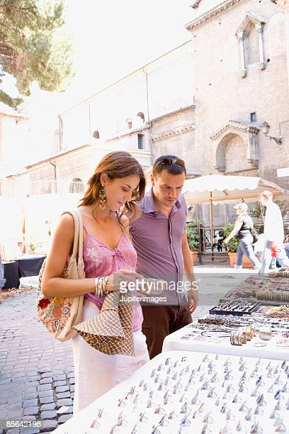 couple looking at items for sale at outdoor market - mid adult women stock pictures, royalty-free photos & images
