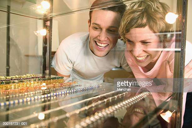 Couple looking at jewellery layed out in glass cabinate, smiling