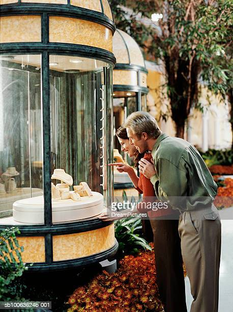 Couple looking at jewellery through shop window, side view