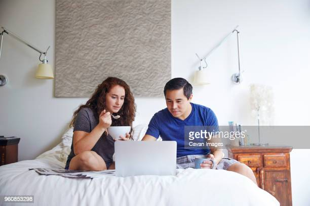 Couple looking at laptop computer while having breakfast on bed against wall