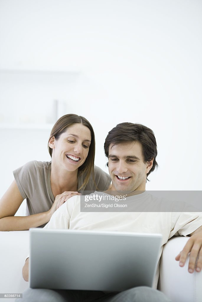 Couple looking at laptop, man sitting in armchair, woman leaning over shoulder : Stock Photo