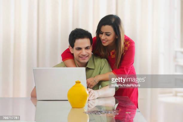 Couple looking at laptop with coins and piggy bank on table