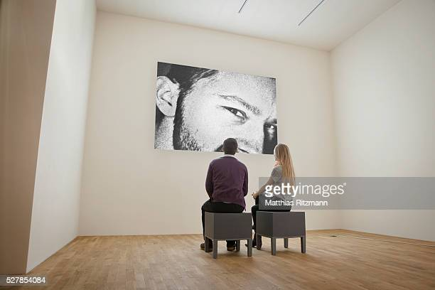 Couple looking at large photograph in gallery