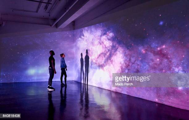 couple looking at large scale projected image of space - innovation stock pictures, royalty-free photos & images