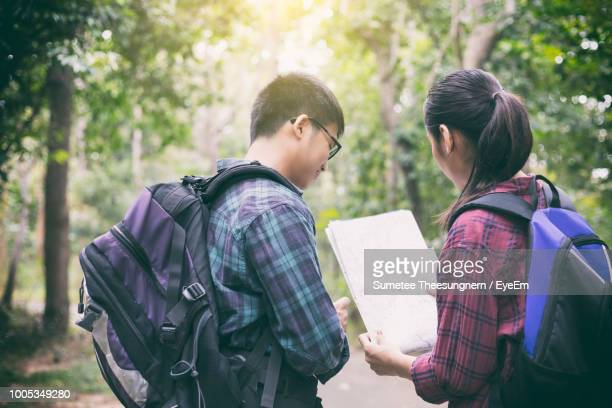 Couple Looking At Map In Forest