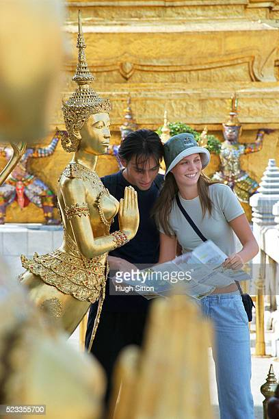 couple looking at map in grand palace, bangkok, thailand - hugh sitton stock-fotos und bilder