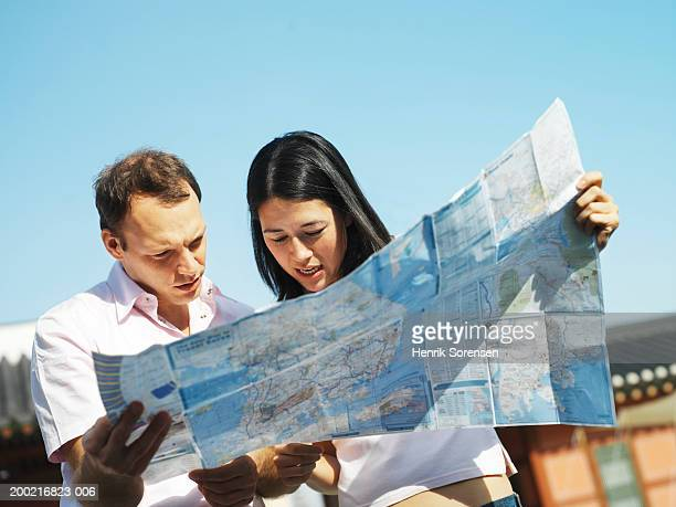 couple looking at map, low angle view - 迷う ストックフォトと画像