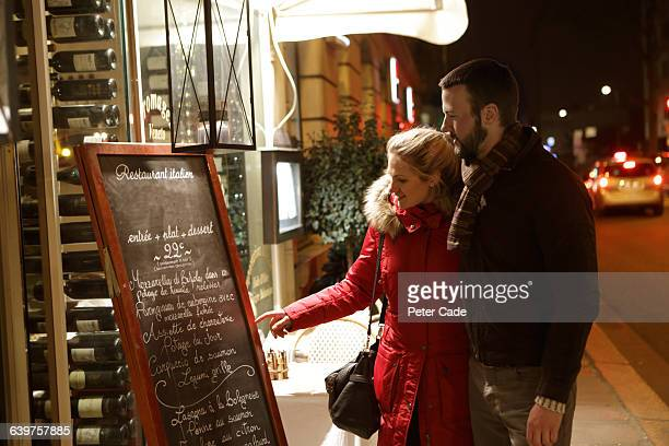 Couple looking at menu outside restaurant