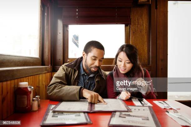 couple looking at menu while sitting in restaurant - menu stock pictures, royalty-free photos & images