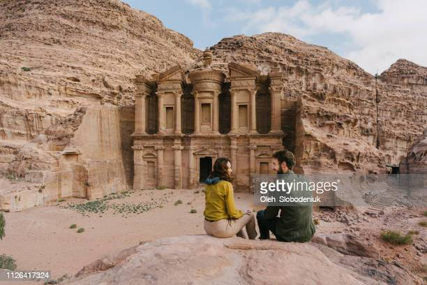 couple looking at monastery in petra - jordan love stock pictures, royalty-free photos & images