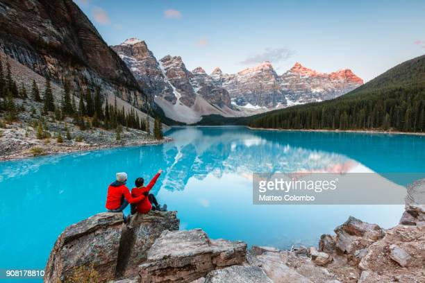 couple looking at moraine lake, banff, canada - canadian rockies stockfoto's en -beelden