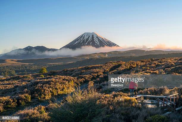 a couple looking at mt ngauruhoe volcano, new zealand. - north island new zealand stock pictures, royalty-free photos & images