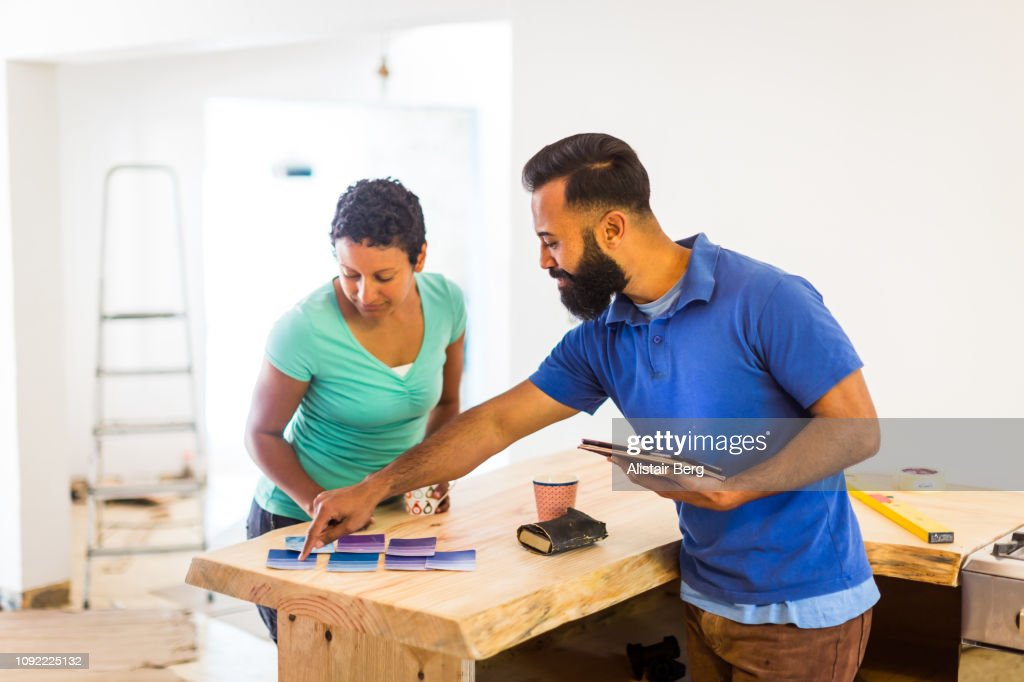 Couple looking at paint samples and a tablet computer : Stock Photo