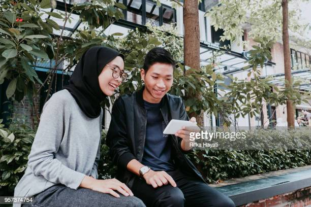 couple looking at phone laughing - rifka hayati stock pictures, royalty-free photos & images