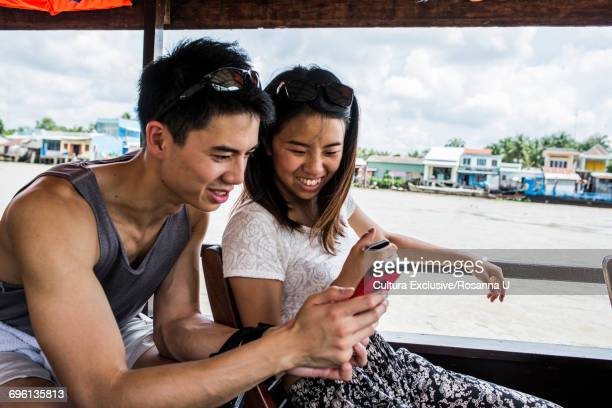 Couple looking at photo in mobile phone on cruise boat, Mekong Delta, Vietnam