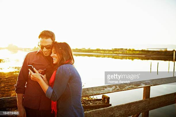 Couple looking at photos on smartphone at sunset
