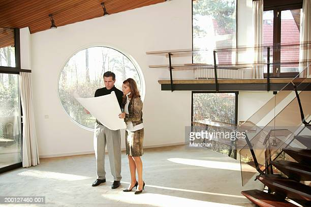 Couple looking at plans in empty house