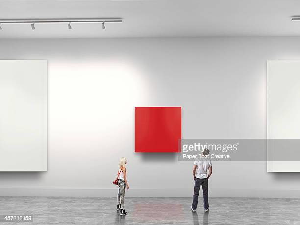 couple looking at red blank art in gallery - galleria d'arte foto e immagini stock