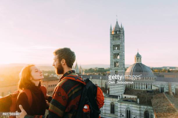 couple looking at scenic view of siena from viewpoint - siena italia foto e immagini stock