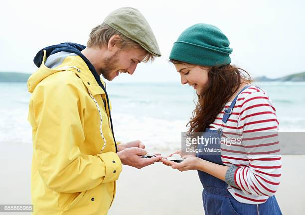 couple looking at shells and stones at beach. - dougal waters stock pictures, royalty-free photos & images