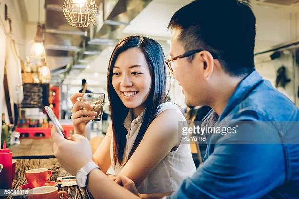 Couple looking at smartphone with smile in cafe