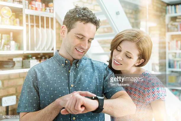 couple looking at smartwatch indoors - wrist watch stock pictures, royalty-free photos & images