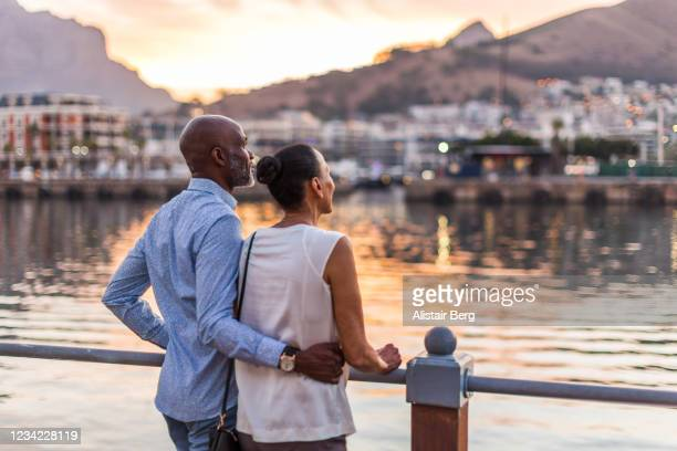 couple looking at sunset at cape town waterfront - travel stock pictures, royalty-free photos & images