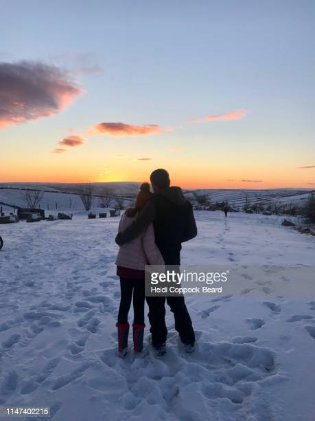 couple looking at sunset in snow - heidi coppock beard stock-fotos und bilder