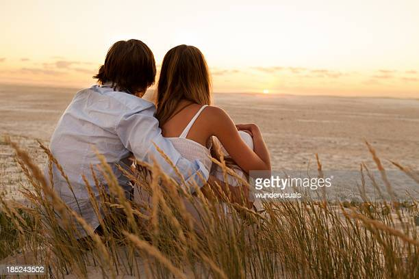Couple Looking at Sunset On Beach