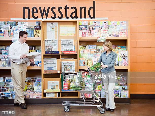 couple looking at supermarket newsstand - news stand stock pictures, royalty-free photos & images