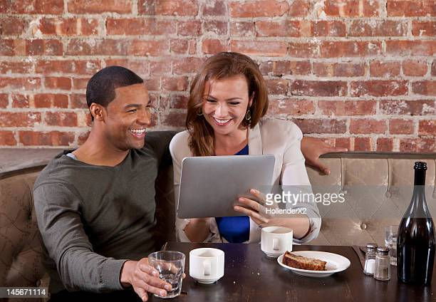 couple looking at tablet at restaurant