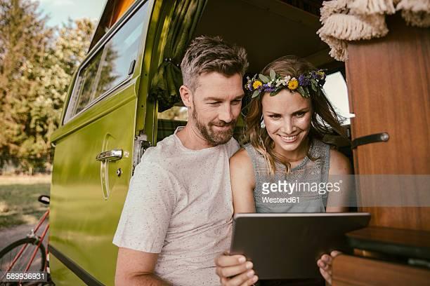 Couple looking at tablet computer in van