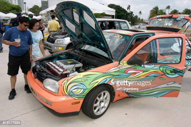 A couple looking at the engine compartment of an electric vehicle at the Miami Goin' Green event