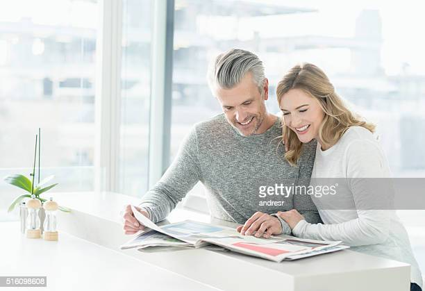 Couple looking at the newspaper at home