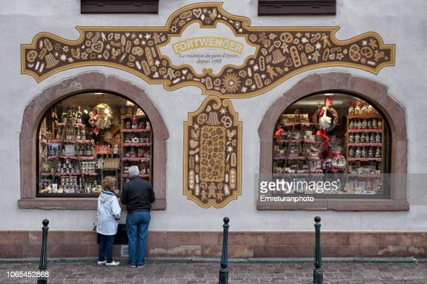 a couple looking at the products at pastry shop windows ,kayserberg village. - emreturanphoto stock pictures, royalty-free photos & images