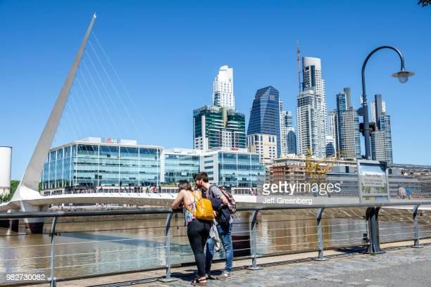A couple looking at the Puente De La Mujer pedestrian suspension swing bridge