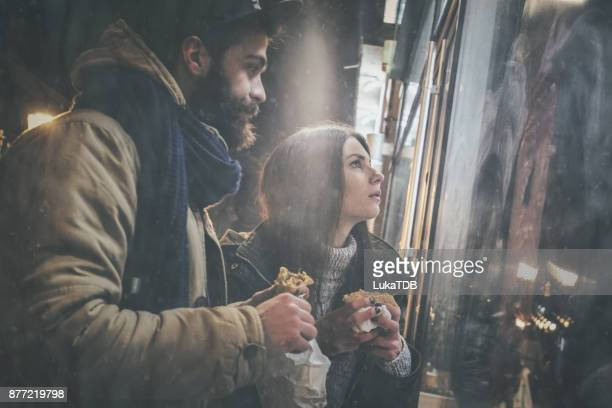 Couple looking at the shop window and eating burger