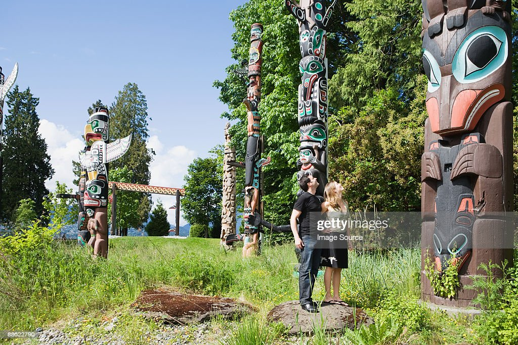 Couple looking at totem poles : Stock Photo