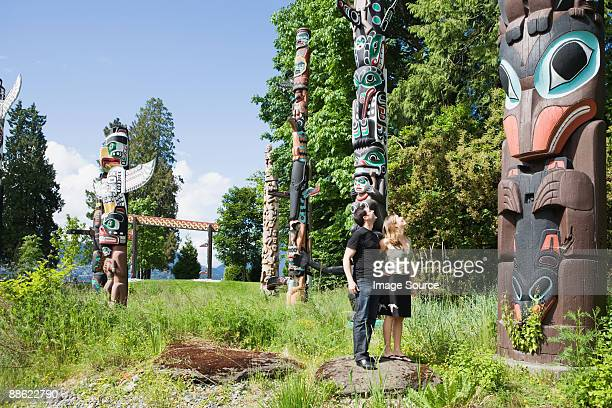 couple looking at totem poles - totem pole stock photos and pictures
