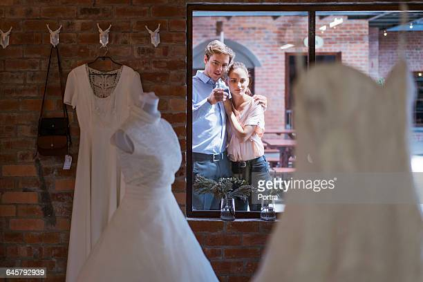 Couple looking at wedding dress seen window
