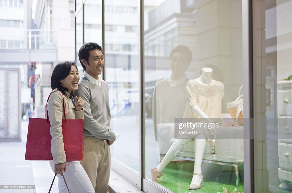 Couple looking at window display and laughing : Stockfoto