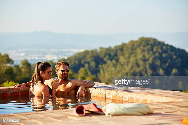 Couple looking away while enjoying in pool