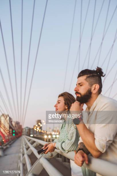 couple looking away while leaning on railing at bridge in city during sunset - leaning stock pictures, royalty-free photos & images
