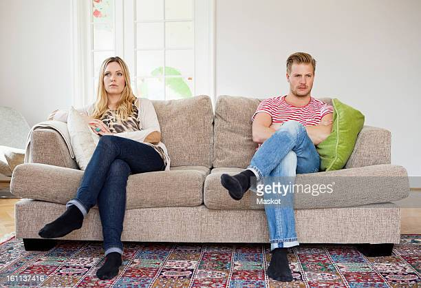 Couple looking away while sitting on sofa with arms folded