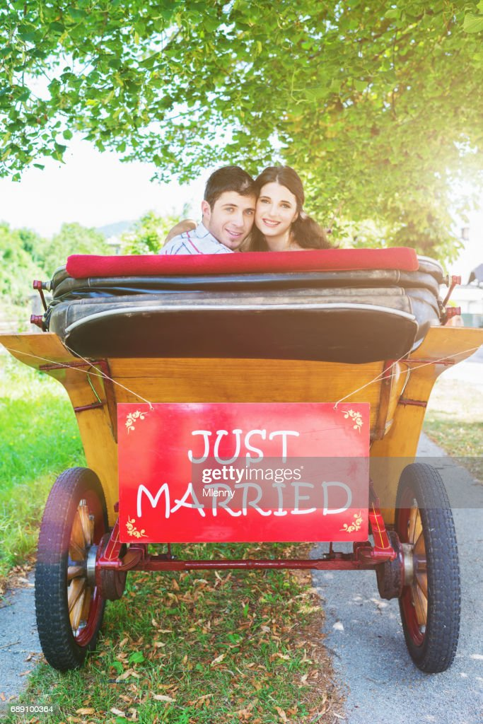 Couple looking back out of horsedrawn carriage with 'Just Married' sign : Stock Photo