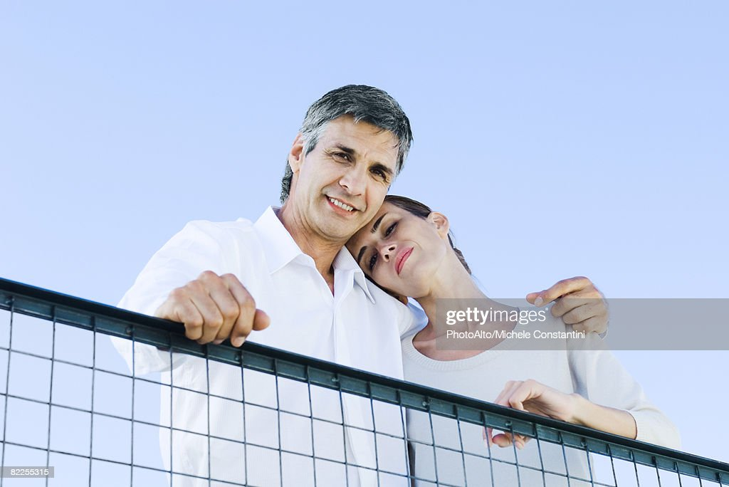 Couple looking down over wire fence at camera, low angle view : Stock Photo