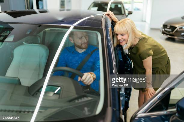 couple looking for a new car in car dealership - test drive stock pictures, royalty-free photos & images