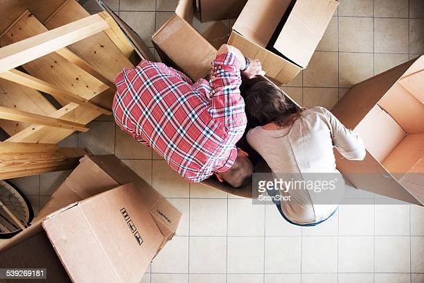 Couple Looking For in Boxes During a Moving
