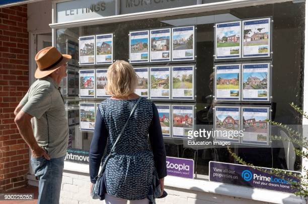 Couple looking in an estate agent's window at properties for sale England UK